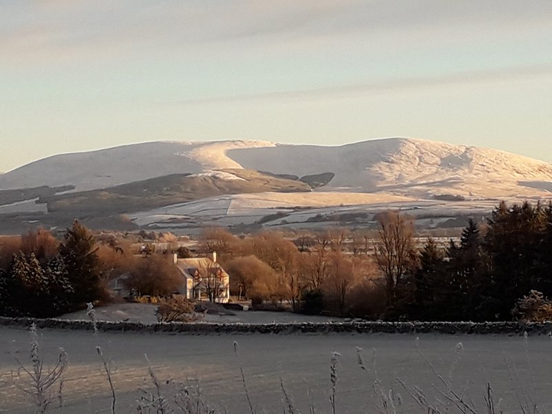 Farmhouse with Cairnsmore under a dusting of snow
