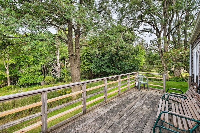 Asseyez-vous sur le porche et profitez de la vue boisée.