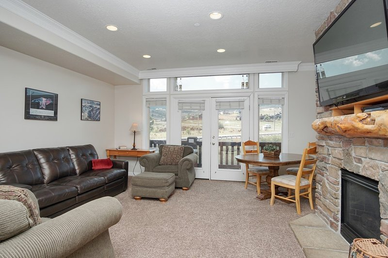 Living Room with Flat Screen TV and Gas Fireplace; Door Leads to the Hot Tub