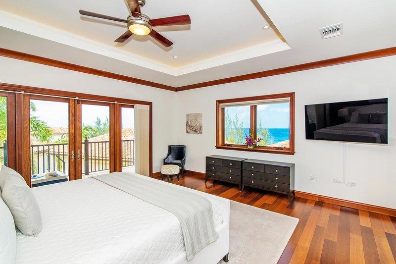 Master suite con vista al mar, cama king, TV y terraza privada.