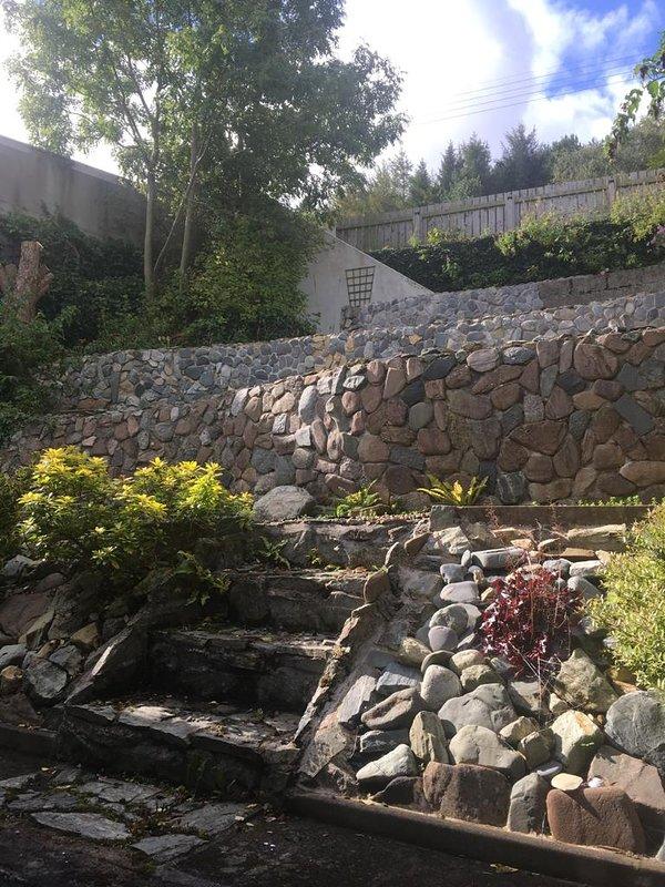 Dit is het uitzicht op de achtertuin. De treden in de linkerbovenhoek leiden u naar het bergpad.