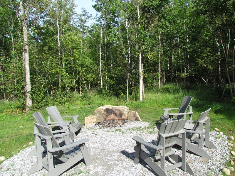 Outdoor fire pit with 6 Adirondack chairs.