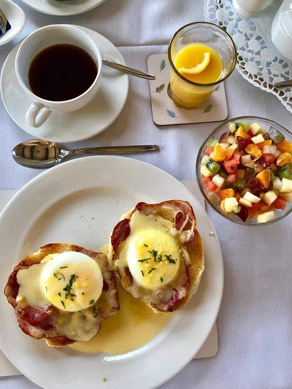 Eggs benedict and fresh fruit salad.