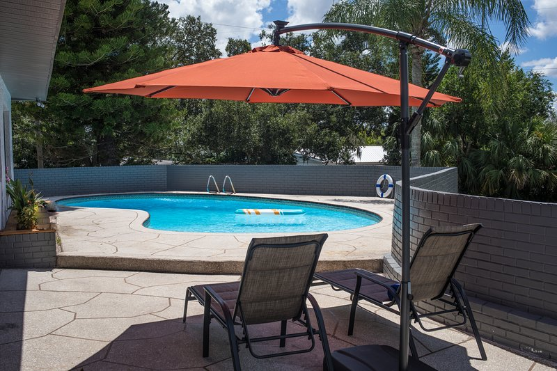 Private Pool deck with lounge chairs, pool umbrella, equipped with life vests, & various pool floats