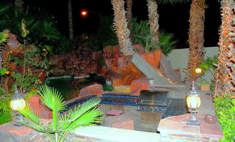 Resort de piscina y zona de barbacoa por la noche.