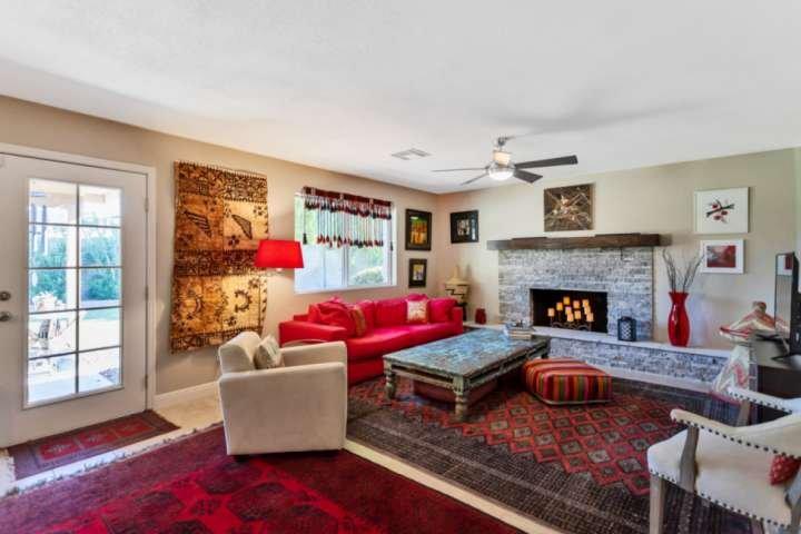 Vacker bohemsk inredning m / dekorativ spis, soffa och platt-TV
