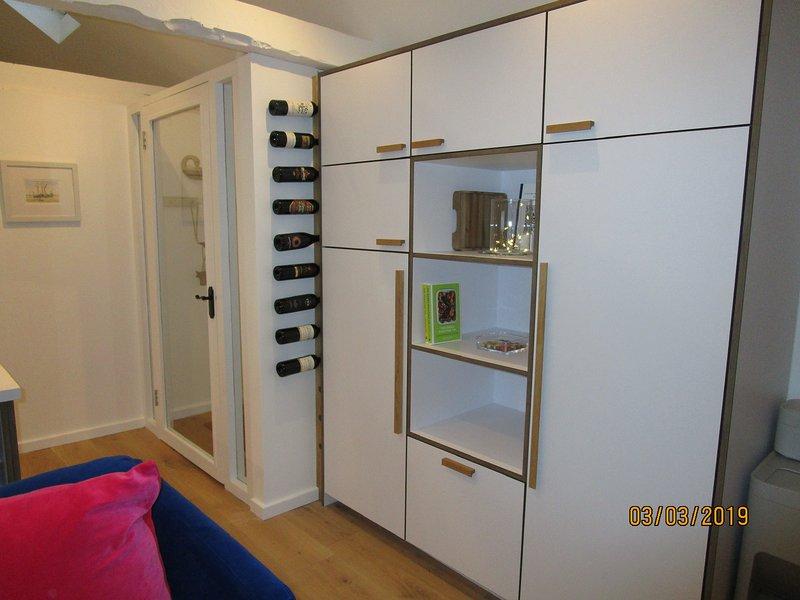 Unidad de cocina con nevera, armario y trastero.