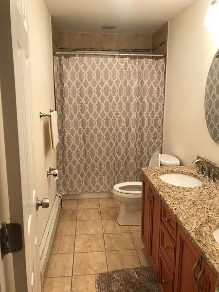 Banheiro no 1º andar com pia dupla, chuveiro / banheira combinados
