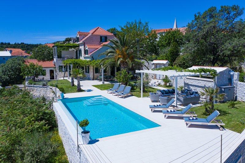 La tradizionale casa in pietra ha un ampio giardino e una piscina a sfioro con vista panoramica sul mare / montagna.