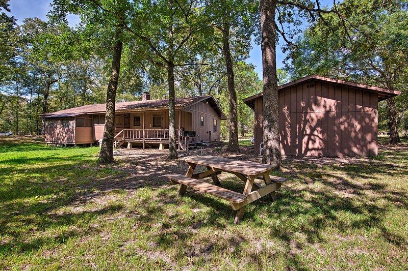 ¡Termine cada día con una fiesta al aire libre en la mesa de picnic de esta cabaña de Broken Bow!