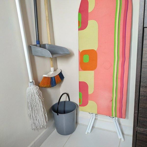 Pièce principale: éléments de nettoyage situés à côté du placard et protégés par un rideau