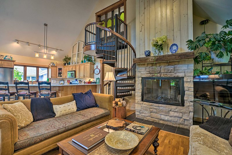 The open living area boasts a stone fireplace and a unique spiral staircase.