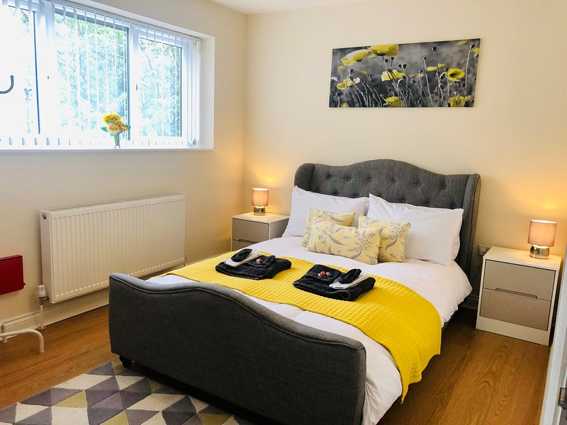 Double bed with bedside tables and touch lamps. Set in cool calming grey and yellow colours.