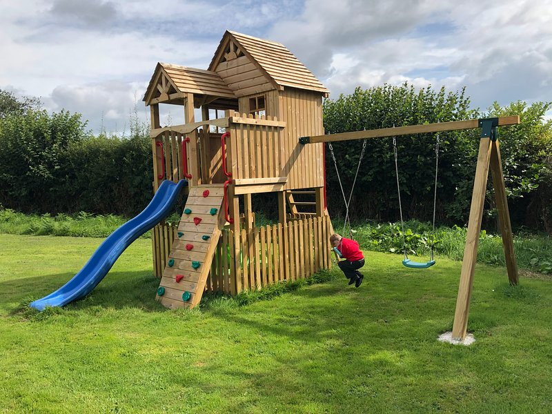 Children's Play area with climbing frame, rock wall, slide, twin swing set and spring rocker