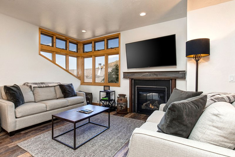 Cozy Main Level Living Room with a Gas Fireplace and 65' Smart TV