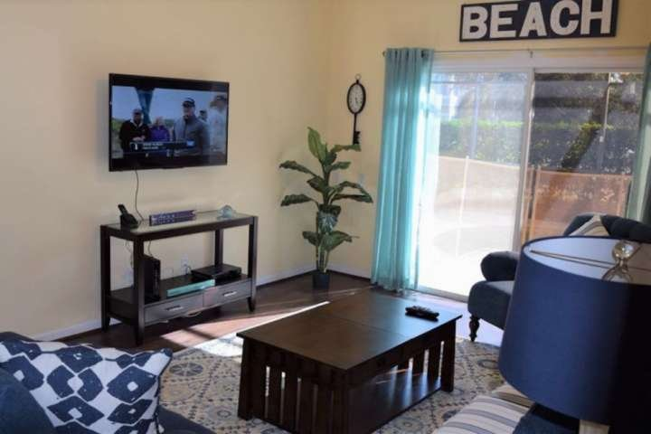 Comfortable Living Area with Wall Mounted TV and Pool Access