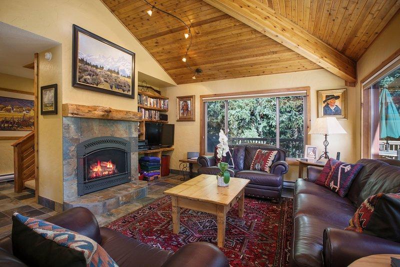 Vue sur le salon avec foyer au gaz et télévision à écran plat.
