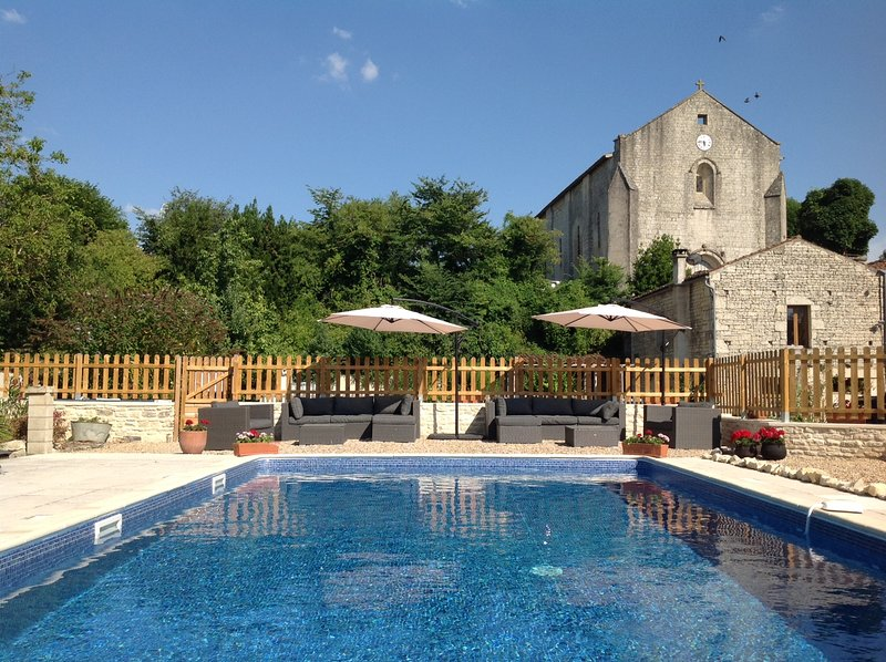 View from the pool of The Farmhouse and church