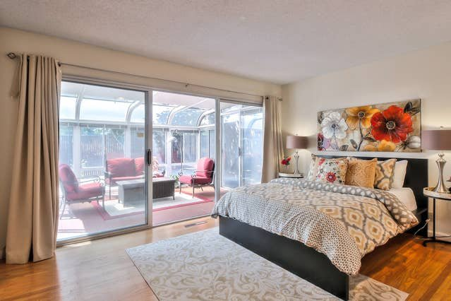 The master suite has an en-suite full bath, as well as easy access to this gorgeous sun room, perfect for lounging.