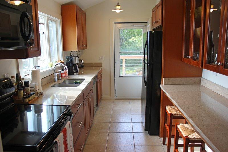 Cocina tipo galera bien equipada con lavaplatos y triturador de basura.