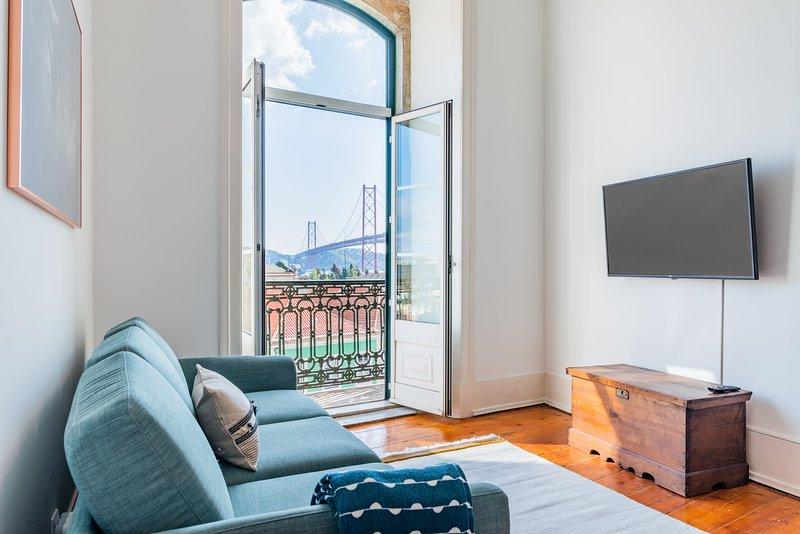 Sala de estar con TV y balcón con vista al río Tajo y al puente 25 de Abril