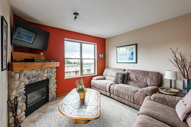 Acogedora sala de estar con muchos asientos y chimenea de gas
