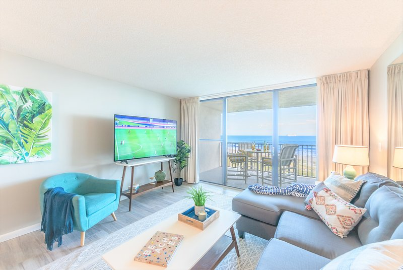 Coastal chic living room with 65' Smart TV, pullout couch and gorgeous views of the water!