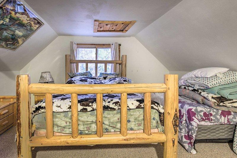 En dubbelsäng och två enkelsängar möblerar detta sovrum.