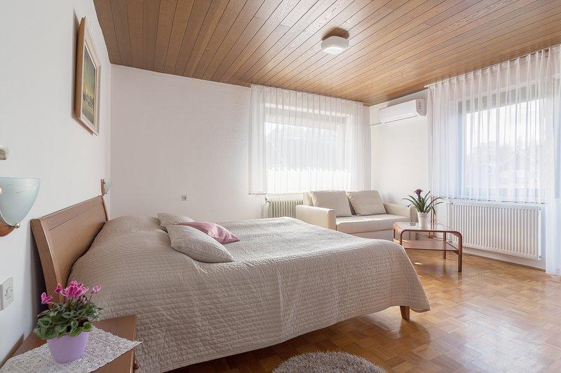 Een groot kingsize bed (180 x 200 cm) en een driezitsbank in de eerste slaapkamer.