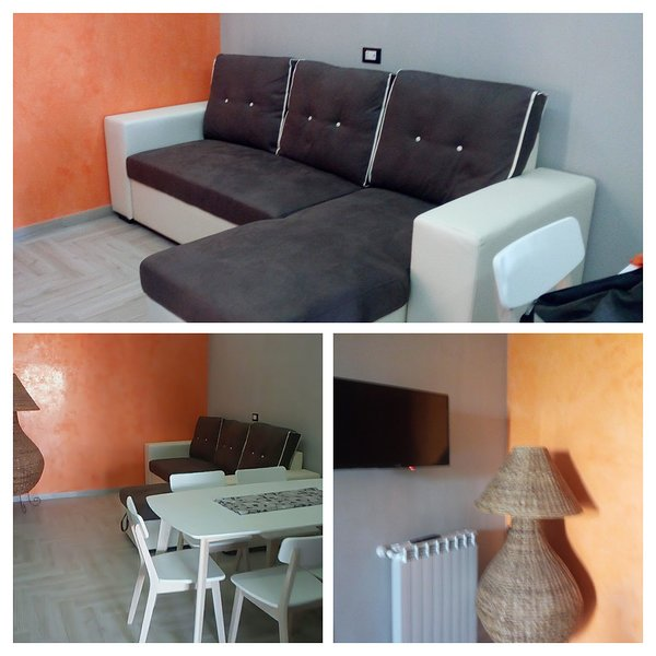 Living room with comfortable double sofa bed with LCD screen and table for convivial moments