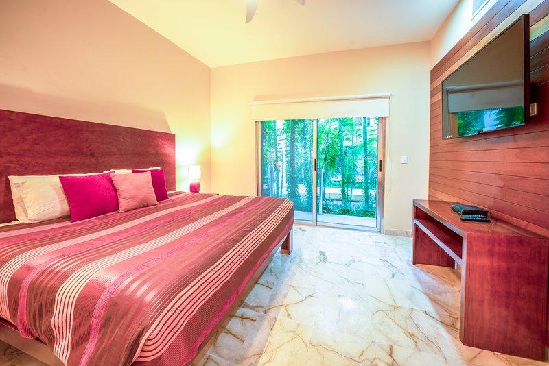Su suite principal con cama King, TV, patio y baño privado.
