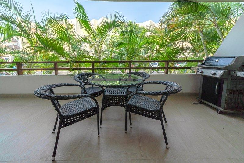 Su patio privado con brisa fresca del mar, barbacoa y juego de comedor al aire libre.