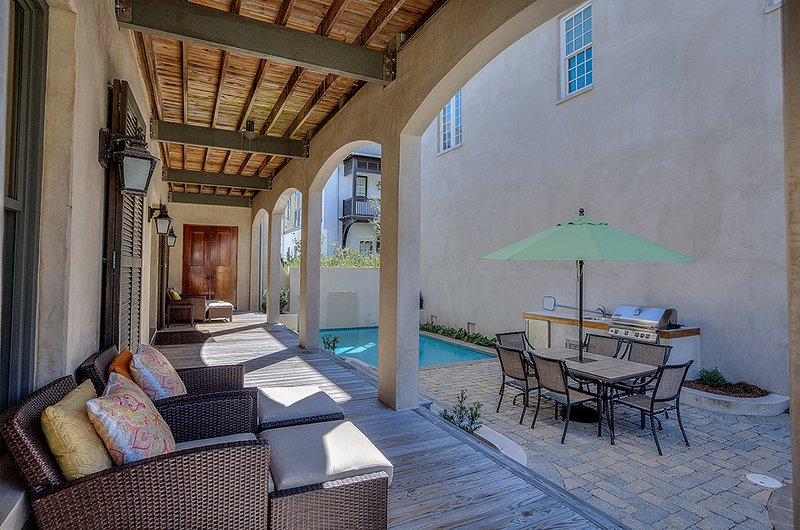 Outdoor Table, Chairs, Umbrella, the Pool, and Lounge Chairs in the Porch.
