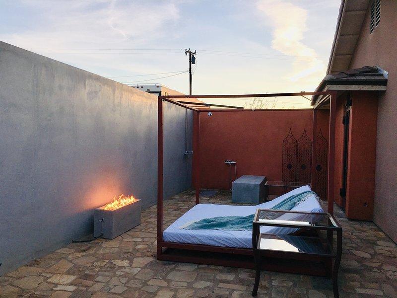 Patio privado al aire libre con ducha, cama king-size y chimenea, junto a la suite principal.