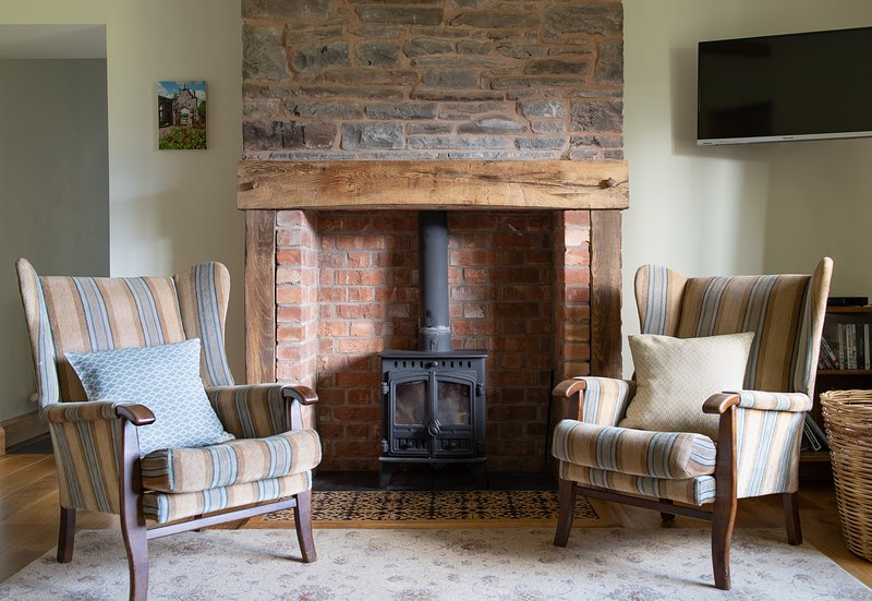 La sala de estar con estufa de leña y azulejos de Treberfydd House