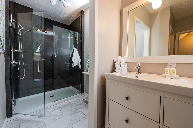 Large walk in shower with bench, Double vanity & private toilet nook.