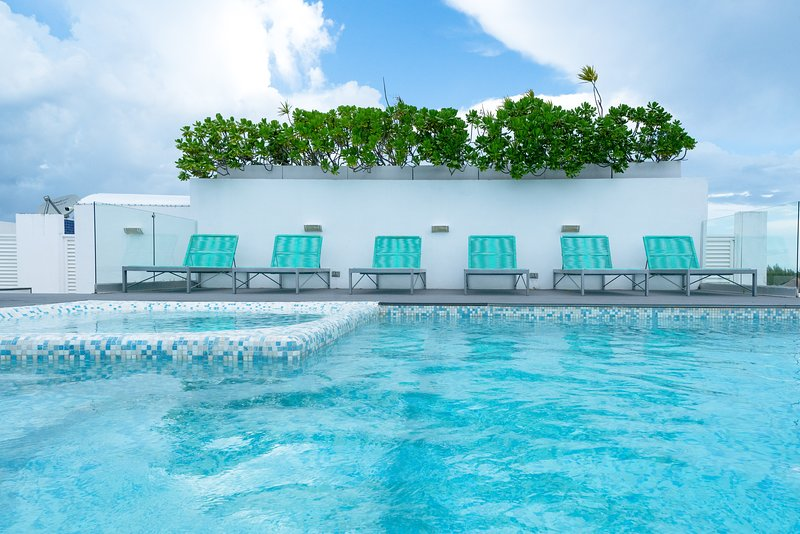 The Deva Condos community rooftop pool with lounge chairs, beds and ocean view