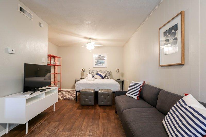 Sala de estar con sofá cama y TV inteligente grande.