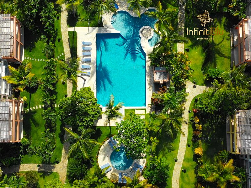 Lush greenery garden with a pool from a bird's eye views, just a few steps from the beach.