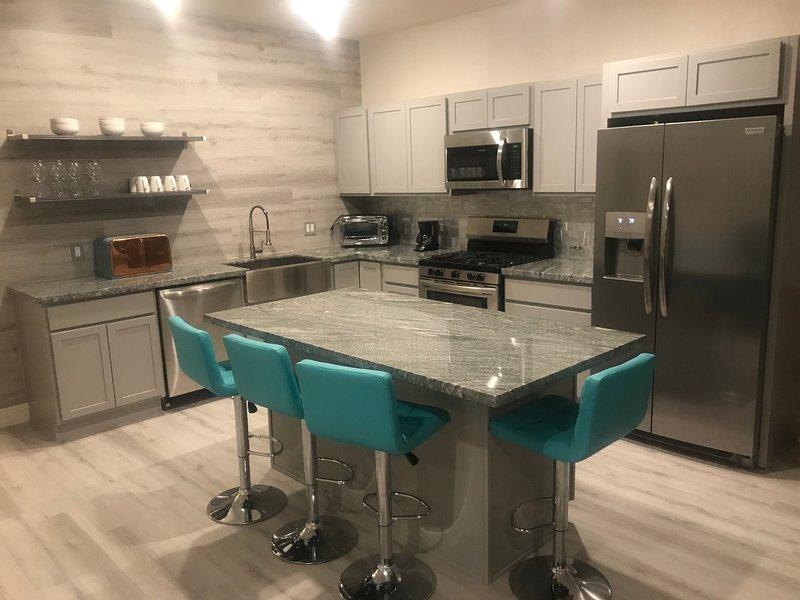 Une cuisine moderne et ouverte avec une cuisinière à gaz, des comptoirs en granit et quatre sièges.