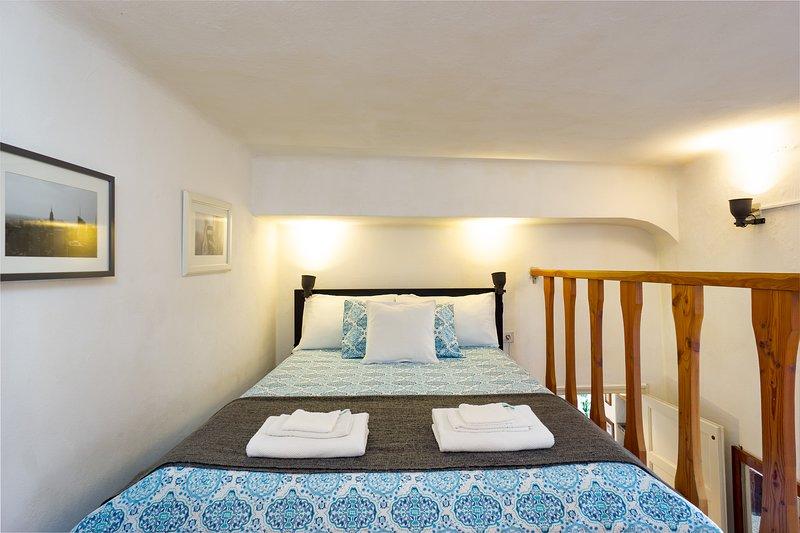 Cama cómoda en una acogedora zona de dormitorio tipo loft.