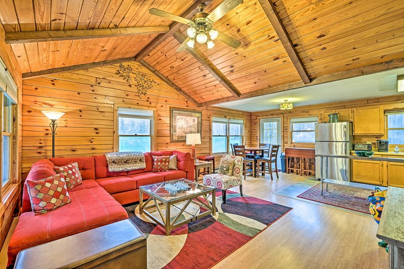 Les hauts plafonds et les poutres apparentes ajoutent une atmosphère chaleureuse au salon.
