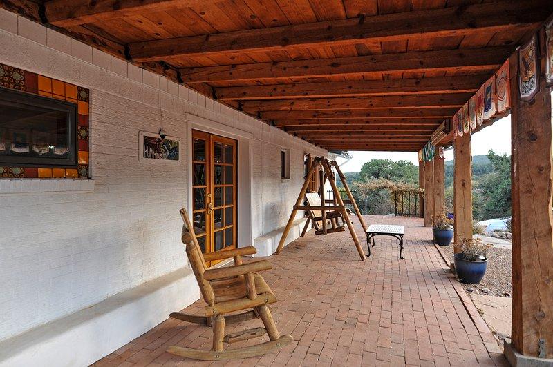 balancín de madera y banco oscilante en el porche delantero