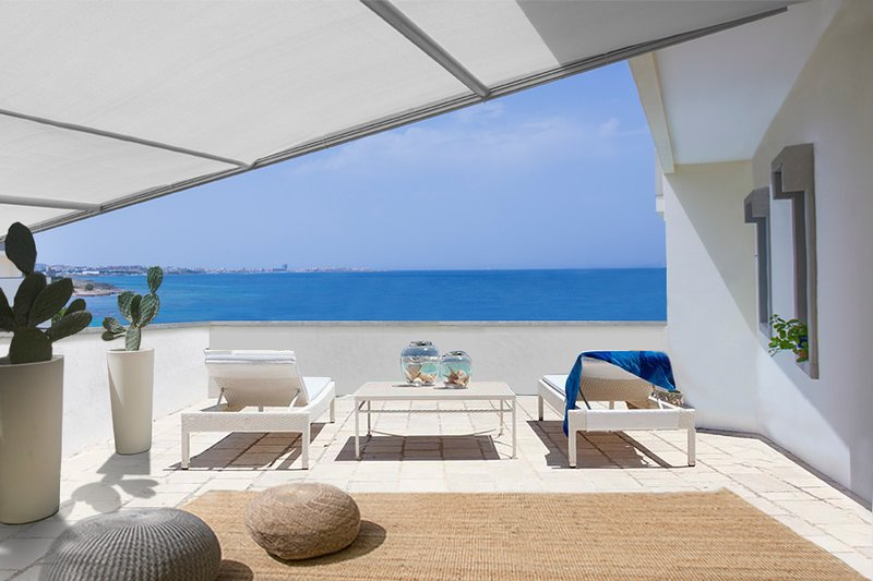 The private landscaped sun terrace adjacent to the suite's living room with stunning sea views