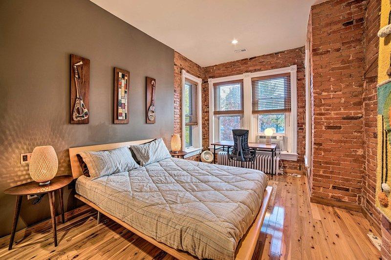 O quarto possui uma cama queen e vários espaços de trabalho para laptop.