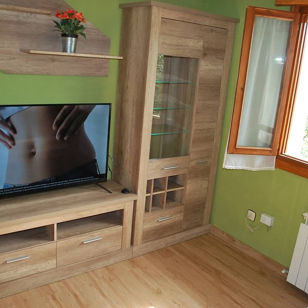 Living room with sofa-cheslong and large flat tv