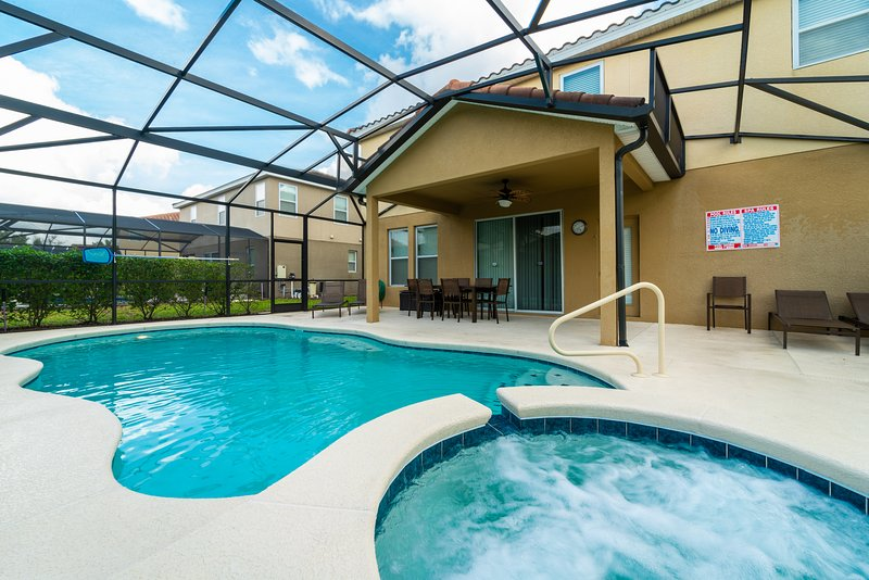 Large pool deck with shaded lanai area and patio table