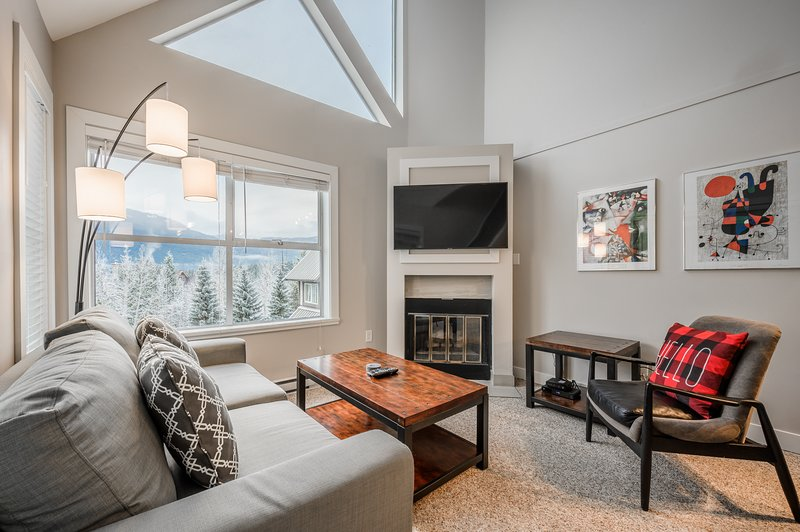 Spacious living area with high ceilings offers a gas fireplace, pull-out sofa and Smart TV.