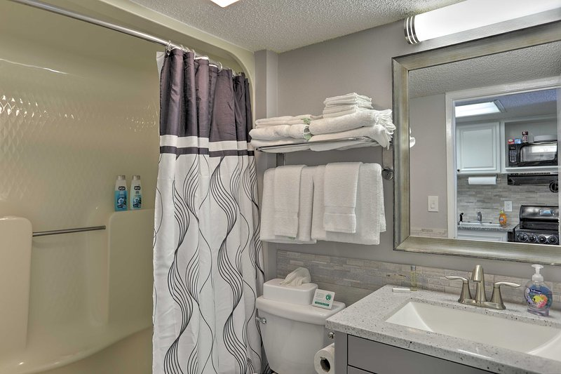 The condo's bathroom features a shower/tub combo and plenty of towels.
