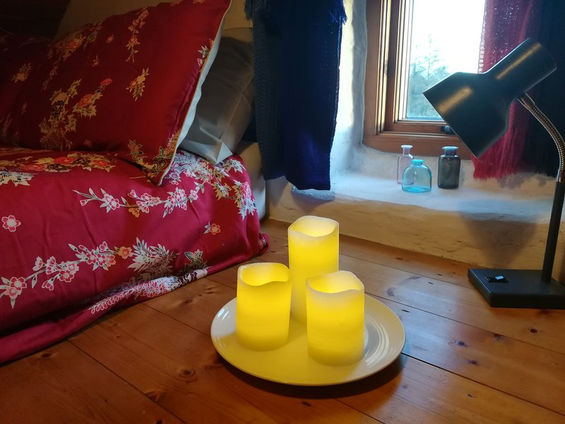 Battery operated candles beside bed, they can be set on timer so they turn off themselves if needed!